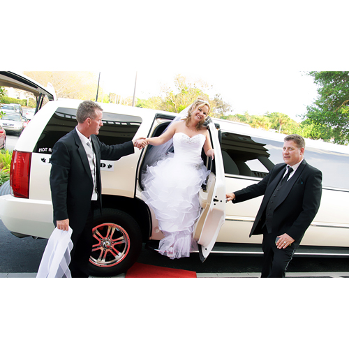 Picture of one of our chauffers escorting a bride and groom out of the vehicle at a church in Clarendon Hills