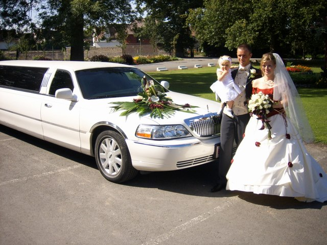 Picture of a bride and groom next to our vehicle after getting married at a church in Willowbrook, IL